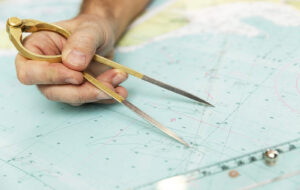 The-Captain-Measures-The-Dista-346234711-300x190 The Captain Measures The Distance On The Map With A Compass. Clo